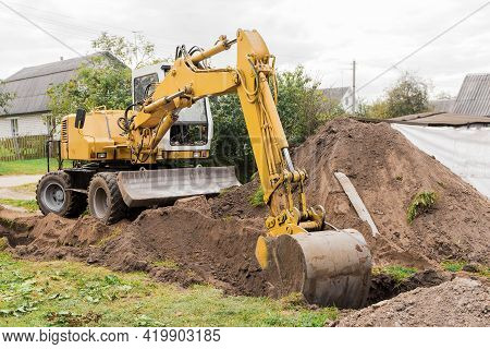 A Hydraulic Piston And A Bucket Excavator Dig The Ground Next To A Pile Of Sand On An Industrial Sit