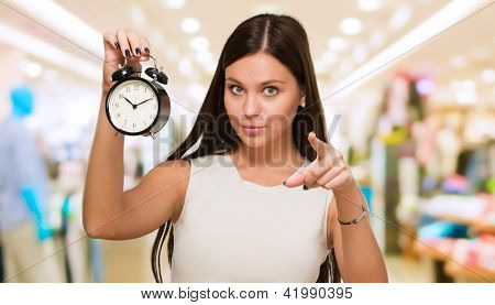 Young Woman Holding Clock And Pointing at a mall