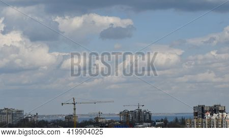Construction Crane Jibs Over Rooftops Under Cloudscape. Under Construction Condo Buildings In Europe