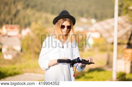 Young Blond Woman In Black Hat And Sunglasses Sets The Ride Mode On The Touch Panel. Stylish Girl Ri