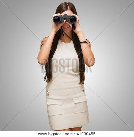 Portrait Of A Young Woman Holding Binoculars against a grey background