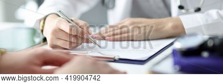 Doctor Advising Patient And Writing In Documents Closeup