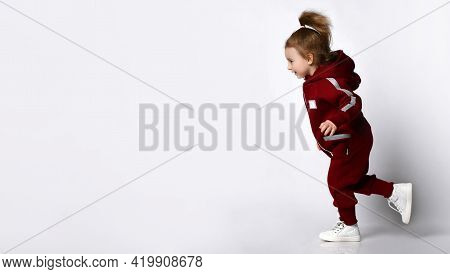 Cute Smiling Little Preschooler Girl Wearing Warm Tracksuit Sportswear With Hood And White Trainers