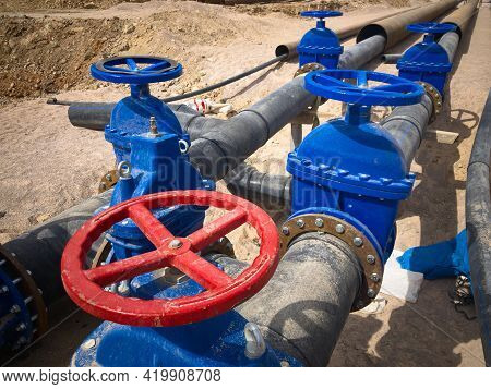 Valves On The Underground Pipeline. Pipe Valves In Trench.