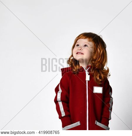 Smiling Positive Little Red-haired Curly Girl In A Sweater With A Zipper And Pockets Looks At The Co