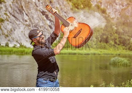 Mad Guitarist Plays Smoking Guitar Near Forest River.