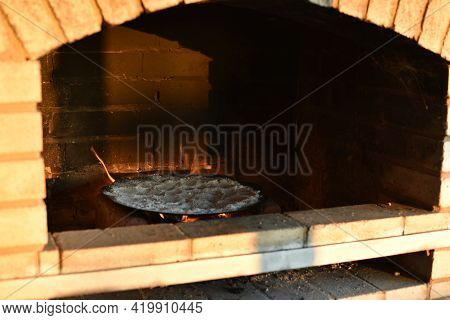 Frying Pan With Salt In The Fireplace. Cleaning A Frying Pan Over A Fire By Roasting Salt