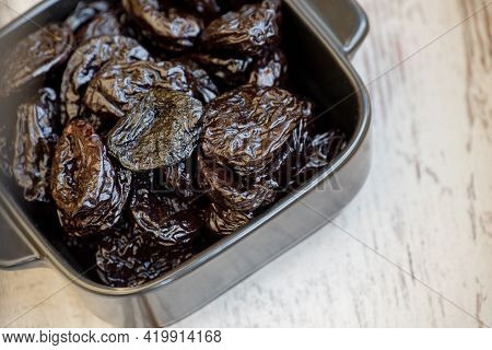 Prunes Group In Wooden Bowl. Dried Prunes In A Plate