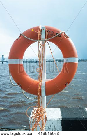 A Life Preserver Hangs On The Pier On The River Bank.