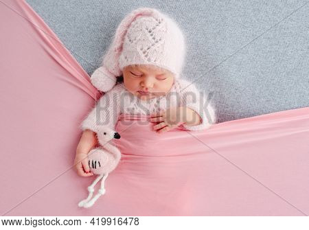 Cute newborn baby girl in knitted hat sleeping on grey stylized background and holding flamingo toy in her hands. Adorable infant child napping under pink blanket during studio photoshoot