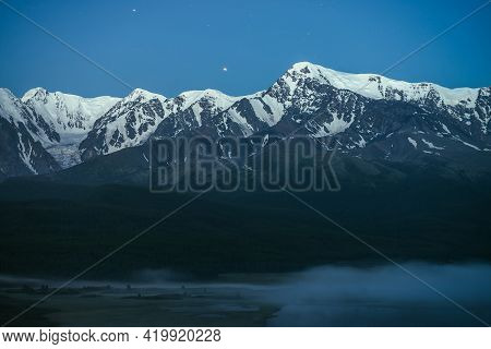 Atmospheric Landscape With Dense Fog On Lake And Great Snowy Mountain Ridge Under Night Sky. Alpine
