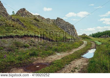 Scenic Alpine Landscape With Dirt Road Along Rocks In Highlands. Puddle On Road Near Rocks And Lush