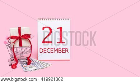 21st Day Of December. A Gift Box In A Shopping Trolley, Dollars And A Calendar With The Date Of 21 D