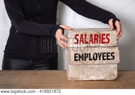 Employees And Salaries Concept. Woman Builds A Pile Of Bricks On A Wooden Table