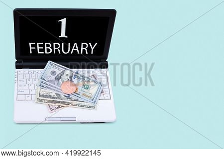 1st Day Of February. Laptop With The Date Of 1 February And Cryptocurrency Bitcoin, Dollars On A Blu