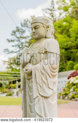Stone Carved Standing Buddha At Entrance To Temple With Blurred Background.