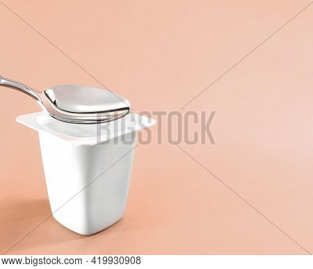 Yogurt Cup And Silver Spoon On Beige Background, White Plastic Container With Yoghurt Cream, Fresh D