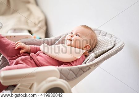 Young Mother Feeding Her Baby Daughter With Fruit Puree. The Baby Is 7 Months Old, Lying In A Specia
