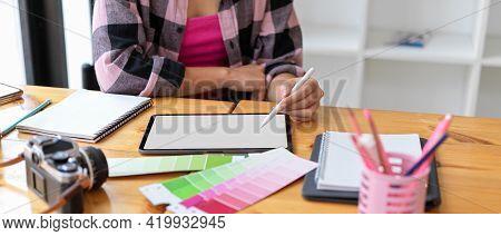 Female Designer Student Doing Assignment On Digital Tablet And Designer Supplies