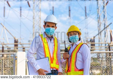 Female Engineers And Staff Work In The High-voltage Substation Area Wearing A Mask To Prevent The Co