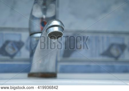 Dripping Old Faucet In Bathroom. Water Dripping From A Tap Into White Sink, Close-up Bottomview. Rec
