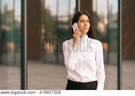 Portrait Of A Pretty Woman Speaking On The Phone Wearing White Business Shirt. She Is Solving, Negot