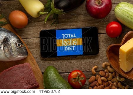 Total Keto Carb Manager app for diet calorie counter on smartphone. Diet Plan On Tablet Pc And Vegetables. Belgorod , Russia - AUG, 18, 2020: