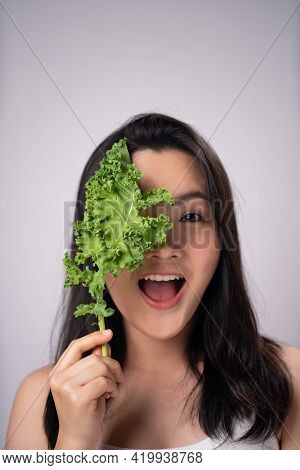 Happy Asian Woman With Kale Leaf Isolated Over White Background. Healthy Lifestyle With Clean Food C