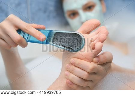 Woman Is Peeling Her Foot And Toes Using Peeler Sitting In Bathroom At Home, Closeup View. Spa Beaut