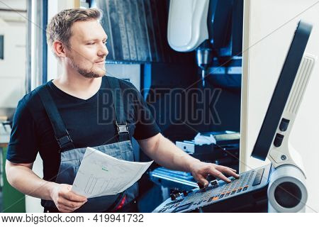 Machine operator programming modern industrial cnc lathe