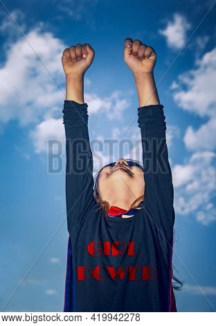 Cute Little Super Girl with Raised Up Hands over Sky Background. Girls Power. Conceptual Photo of an Equality of Rights Between Men and Women.