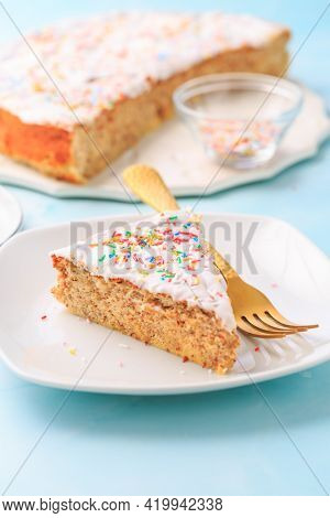 Homemade gluten-free almond case with lemon icing and sugar sprinkles on plate