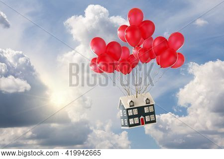 Toy House With Red Balloons Floating In The Blue Sky With Sunshine And White Fluffy Clouds. Soaring