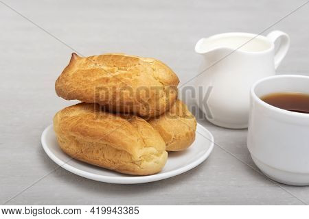Homemade Eclairs And Tea With Milk. Traditional French Eclairs. Profiteroles On White Saucer