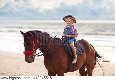 Kids Riding Horse On Beach. Children Ride Horses. Cute Little Girl On Pony On A Ranch. Child And Ani