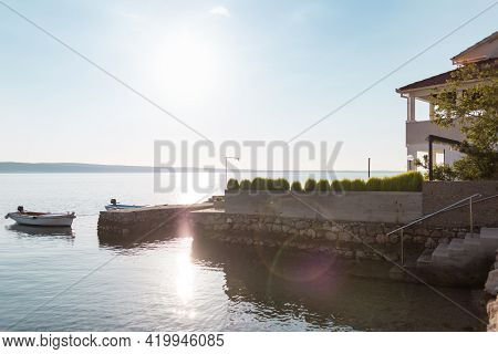 House On The Seaside. Mansion In The Resort Town. Boat On The Pier Near A Large House With A Terrace