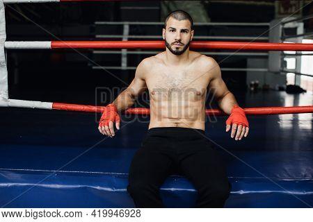 Fighter Practicing Some Kicks With Punching Bag. Kick, Punching Bag On Dark Background. Black Punchi