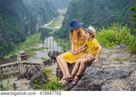 Mother And Son Tourists On The Lake Tam Coc And Pagoda Of Hang Mua Temple, Ninh Binh, Viet Nam. Its