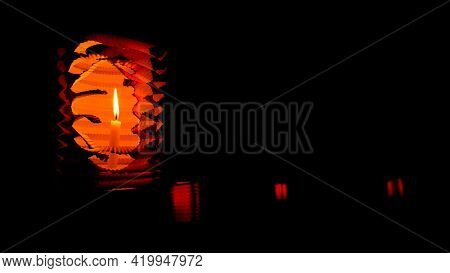 Orange Lamp With A Burning Candle On A Black Background.