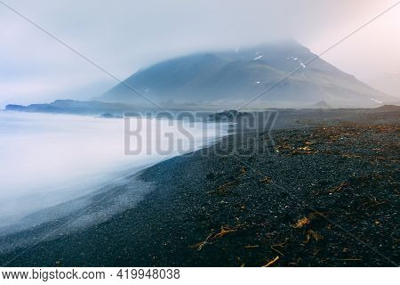 Typical Black Volcanic Beach On The Iceland. Sea And Mountain In The Fog .
