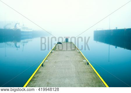 Iceland Harbor In The Fog With Pier And Ship, Iceland.