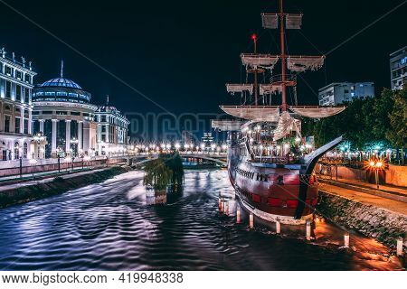 Night Photo Capital City Skopje. City Center And River Vardar. On The Right Is Large Ships, Which Us