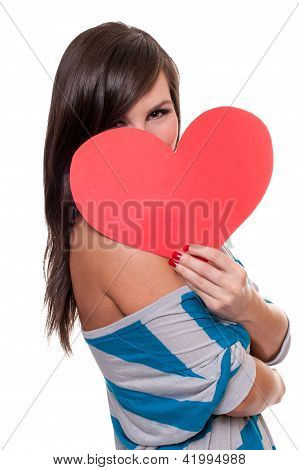 Pretty girl hiding behind Valentine's day heart isolated on white