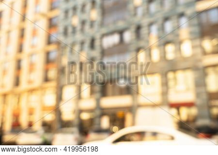 Abstract Blurred Building With Illuminated Facade Exterior At The Sunset. Blurry Modern Building Wit