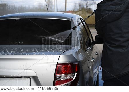 A Worker Washes The Rear Window Of A Gray Car With A Jet Of Water From A High-pressure Car Wash At A