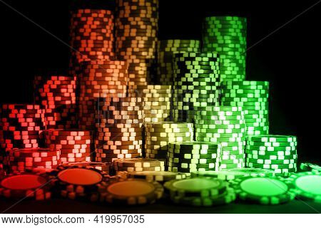 Stack Of Poker Chips On A Green Gaming Poker Table At The Casino. Poker Game Concept. Chips For Poke