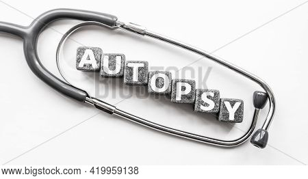 Stone Block Form Word Autopsy With Stethoscope. White Background. Medical Concept. Surgically Openin