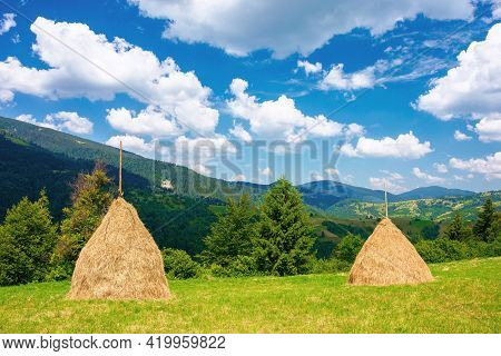 Rural Landscape With Haystack On The Grassy Meadow. Wonderful Mountain Scenery On A Sunny Day In Sum