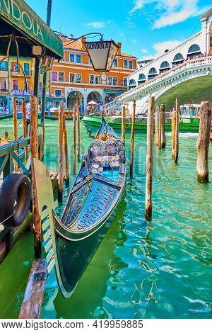 Venice, Italy  - June 15, 2018: Gondola on the Grand Canal next to Rialto bridge in Venice