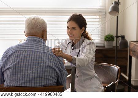 Smiling Female Doctor Touch Elderly Male Shoulder Reassure Give Hope